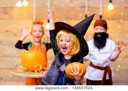 Happy group of pirate and witch children during Halloween party playing around the table with pumpkins