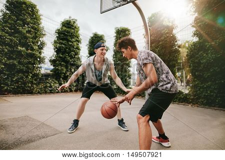Teenagers Playing Basketball On Outdoor Court
