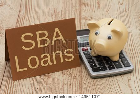 Getting a SBA Loan A golden piggy bank card and calculator on a wood background with text SBA Loans