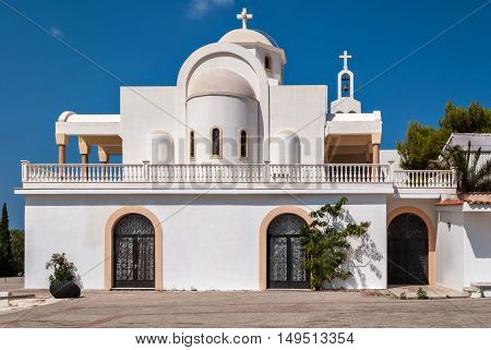 View of the Orthodox church with white walls in the Greek village of Anavisos in the summer sunny day.