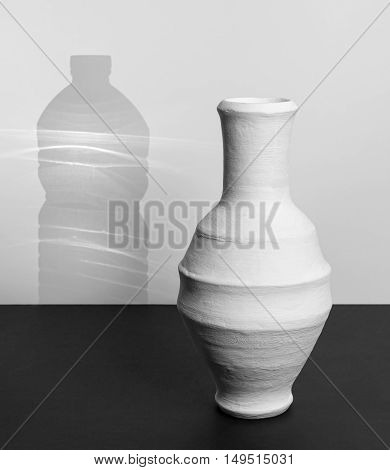 White Egyptian traditional pottery drinking jar (Arabic: Kolla) with shadow of a plastic water bottle