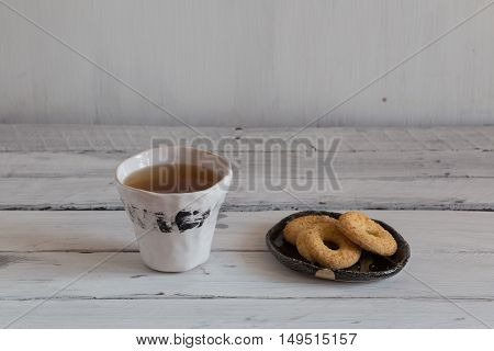 white ceramic cup with a black stripeblack and white hand-made ceramic tableware cookies on a ceramic plate tea with sweet dessert.