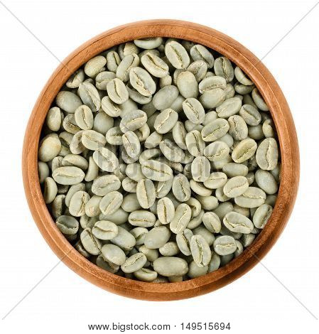 Green Arabica coffee beans in a wooden bowl on white background. Unroasted pits of the coffee cherries. Isolated close up macro food photo from above.