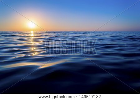 Sunset over the sea. The sun reflected off the waves. Smooth waves. Clear sky