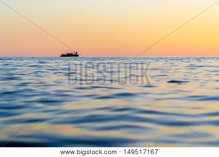 Evening seascape. Silhouette of man on the row boat in the sea. The sunlight reflected off the waves. Georgia