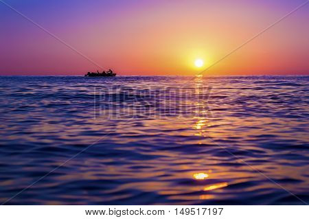 Evening seascape. Silhouette of man on the row boat against the setting sun. The sun reflected off the waves. Purple pink and yellow colors. Georgia
