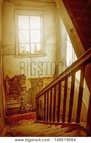 The flight of stairs to a window in an old abandoned house.