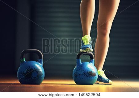 Fitness woman training by kettlebell in the gym.