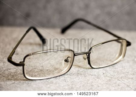 Men's glasses with a thin rim on a gray background closeup