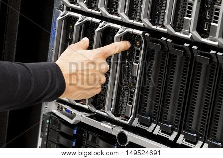 Closeup of IT technicians hand touching power button on blade server at data center