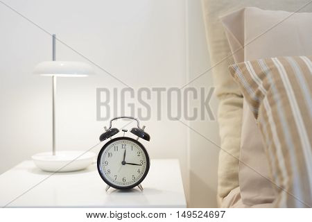 Alarm clock and lamp on a nightstand