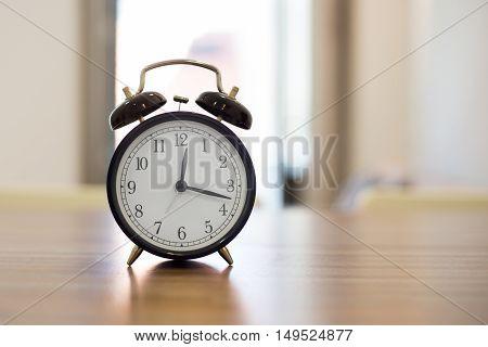 A black larm clock on the nightstand