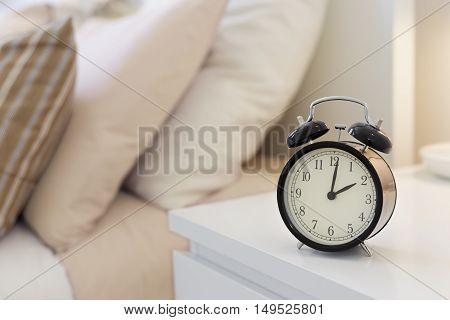 A black alarm clock on the nightstand