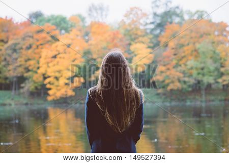 Outdoor autumn portrait of girl standing backwards with straight hair. Back view of woman explores calm lake and forest nature at fall. Image toned with old film style filters