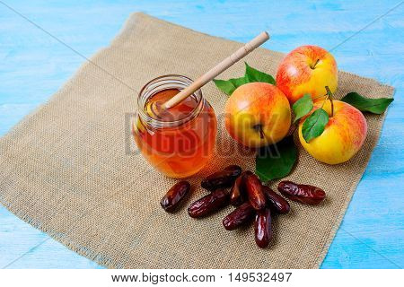 Honey jar dates and apples on blue wooden background. Rosh hashanah concept. Jewesh new year symbols.