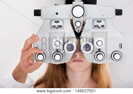 Close-up Of An Optometrist's Hand Adjusting Phoropter For Girl