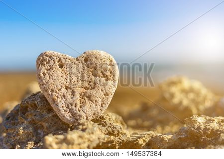 Stone heart on the pebble beach in the background the sea close up.