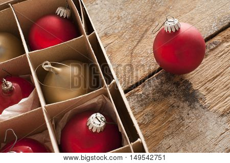 Red and gold Christmas baubles in a brown cardboard box with a single red ball outside on a rustic wooden table with copy space for a seasonal greeting