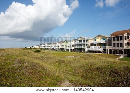 Wide angle view of luxury beach vacation rental houses on the green sand dunes; Sunset Beach, North Carolina