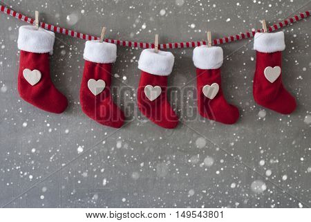Nicholas Boots As Advent Calendar Hanging On A Line. Cement Wall As Modern Background With Snowflakes. Textile Shoes With Hearts.