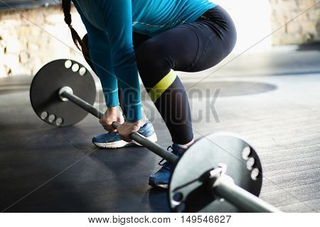 Muscular woman in a gym doing heavy weight exercises. Young woman doing weight lifting at health club.