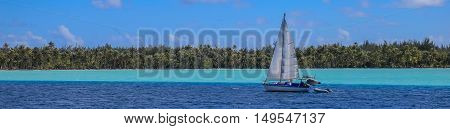 Sailboat in Bora Bora French Polynesia : The two tone sea under the clear sky. The deep blue sea with an island. A dreamed destination for honeymoon.