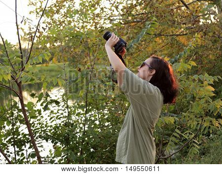 Young woman taking photos with a SLR camera after sunset in a park