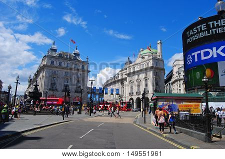 London, United Kingdom - July 7, 2014. View of Piccadilly circus in London, with billboards, people and city traffic, in summer.