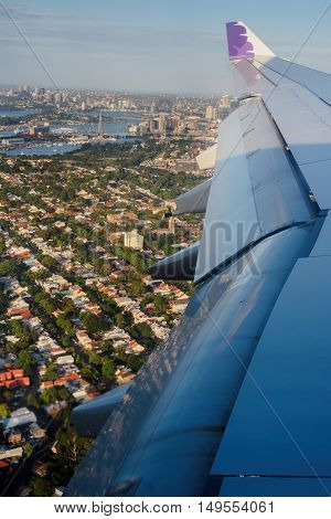 Sydney, Australia - Dec 23, 2015: Onboard Hawaiian Airlines. The plane descends and banks slightly to reveal the harbour and surrounding suburbs. Sydney Harbour Bridge and Pyrmont Bridge can be seen in the distance.