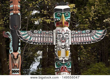 Two colourful Totem Pole with foliage background in Stanley Park. They are located on the eastern point, just before Hallelujah Point on a bright, sunny spring day.