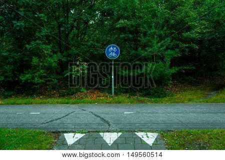 blue bycicle sign on a road in the middle of a forest