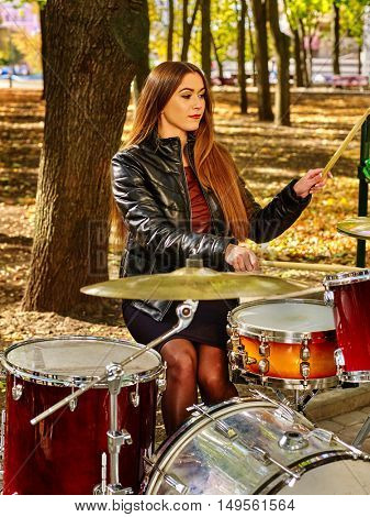 Music street performers on autumn outdoor. Woman drummer playing drum in autumn park.