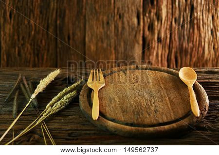 wood dish on old wooden table with spoon set in dining room and prepare for food, vintage wooden dish set with dark picture style, wood dish craft in the restaurant for serve food to the customer.