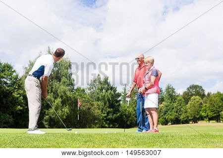 Golf pro practicing the sport with senior woman and man