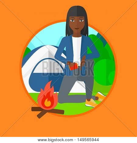 An african-american young woman kindling campfire on the background of camping site with tent. Tourist relaxing near campfire. Vector flat design illustration in the circle isolated on background.