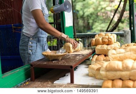 Woman slicing cutting home made soft bread for feeding fish