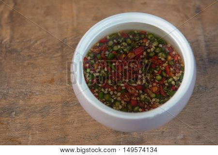 red and green chili Sauce spicy Thailand in a white cup . on wood background