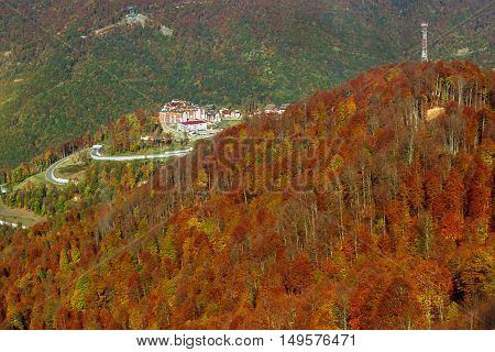 Ski resort with hotel and tourist infrastructure among the mountain massif. Autumn Caucasus mountain landscape views of hills and peaks. Krasnaya Polyana - Alpine ski resort constructed from 2003 to 2011 for Sochi games. Rosa Khutor Sochi Russia