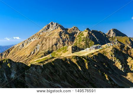 Construction of tourist facilities on top of a hill. Autumn mountain landscape views of hills and peaks of Caucasus mountains. Krasnaya Polyana - Alpine ski resort constructed from 2003 to 2011 for Sochi games. Rosa Khutor Sochi Russia