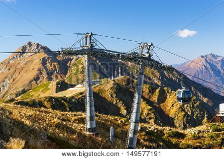 Mountain zipline through autumn forest on backdrop of Caucasus mountains funicular railway to observation deck tops 2320 m. Krasnaya Polyana - Alpine ski resort constructed from 2003 to 2011 for Sochi games. Rosa Khutor Sochi Russia poster