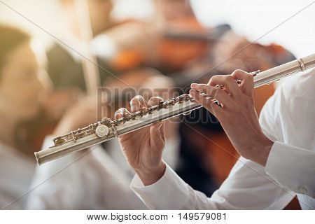 Professional female flute player performing with classical music symphony orchestra unrecognizable person