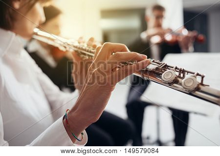 Professional female flustist playing her instrument on stage with classical music symphony orchestra