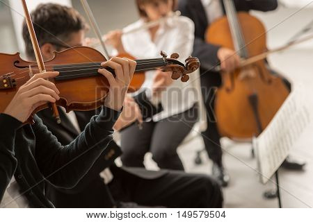 Classical music symphony orchestra performing on stage professional male violinist on foreground teamwork and art concept