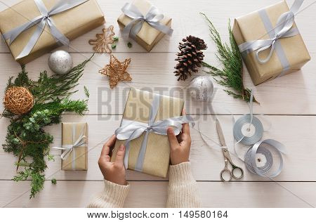 Creative diy hobby. Making bow on modern handmade christmas present, box in stylish paper with satin silver ribbon. Top view of hands on white wood table with fir tree branches, decoration of gift.