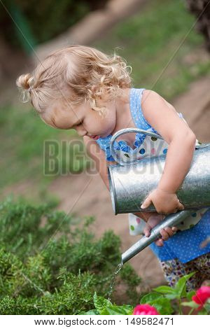 Diligent Pretty Little Girl Watering Flowers In Summer Garden.