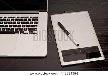 Graphics tablet with a pencil some laptop on black wooden table close-up
