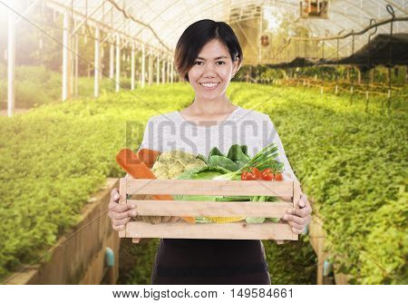 Portrait of a smiling staff woman holding wooden box with fresh organic vegetables from farm