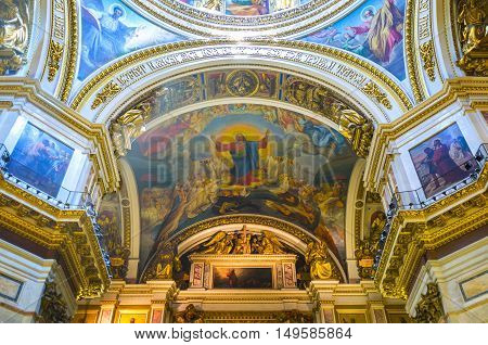 SAINT PETERSBURG RUSSIA - APRIL 25 2015: The splendid rich interior of St Isaac's Cathedral includes painted and mosaic icons covering walls and ceiling surrounded by carved gilt ornaments and old slavonic inscriptions on April 25 in Saint Petersburg.