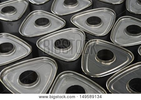 Industrial background. Stacks of new exhausts and silencers mufflers car before distribution and retail. Detail of a new automotive components in stainless steel. Close up.