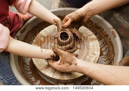 Moulding of a clay pot on a potter's wheel hands
